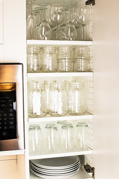organized kitchen cabinets with extra shelves and glassware.