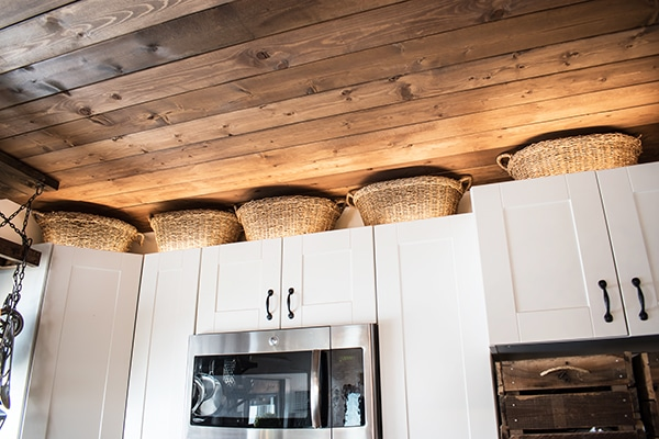 wicker storage baskets on top of white cabinets.