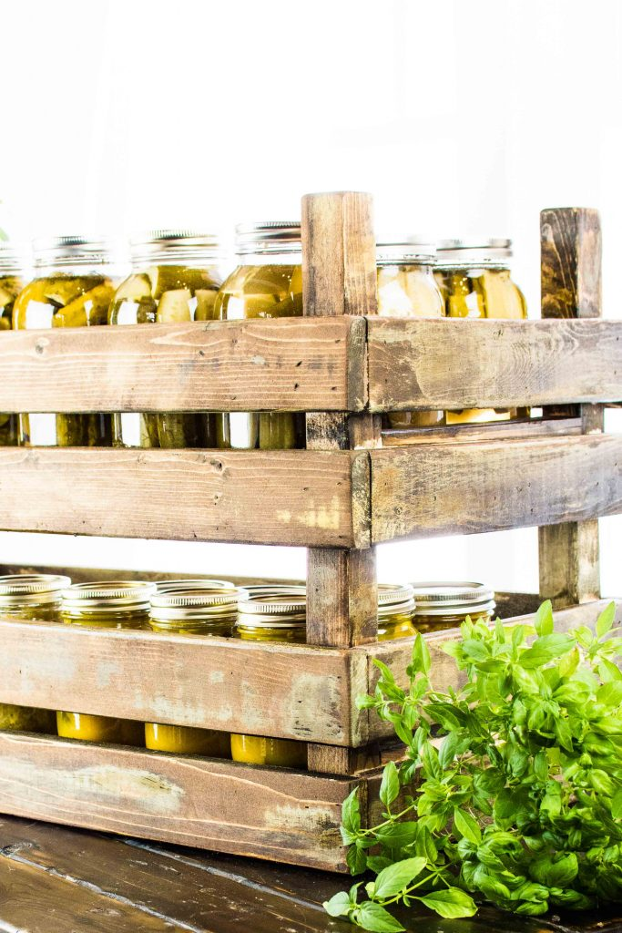 Rustic stackable storage bins filled with homemade pickles in mason jars